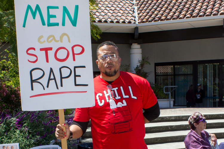 Marcher dawns sign against sexual assault and rape.